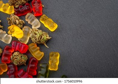 Cannabis edibles, medical marijuana, CBD infused gummies and edible pot concept theme with close up on colorful gummy bears and weed buds on dark background with copy space
