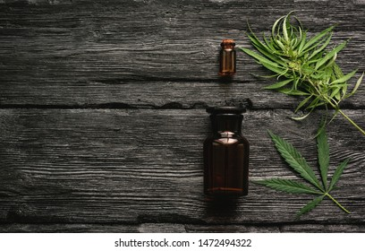 Cannabis essential oil in the bottle and a green stem with leaves on a black wooden table background.