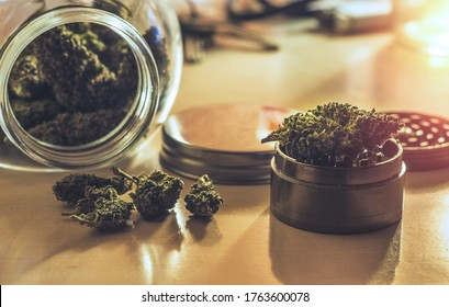 Cannabis flower buds in glass jar and grinder on table