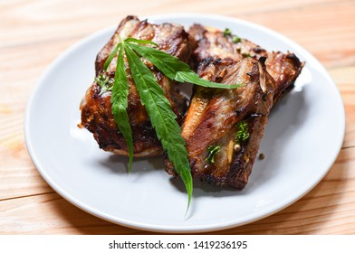 cannabis food with bbq pork ribs grilled with herbs spices served on white plate / Roasted barbecue pork spare rib and marijuana leaf