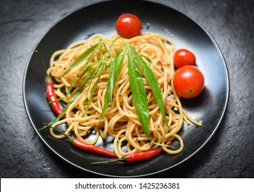 Cannabis food with spaghetti pasta and tomato chilli and  basil leaves vegetables / Traditional delicious Italian food marijuana leaf on top