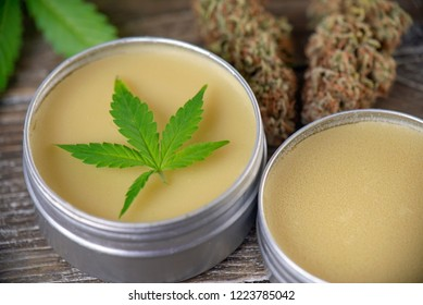 Cannabis hemp cream with marijuana leaf and nug over wood background - cannabis topicals concept