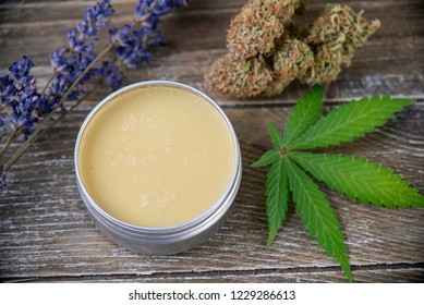 Cannabis hemp cream with marijuana leaf, lavender and nugs over wood background - cannabis topicals concept