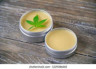 Cannabis hemp cream with marijuana leaf over wood background - cannabis topicals concept