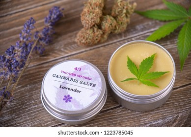 Cannabis hemp cream with marijuana leaves, lavender and nugs over wood background - cannabis topicals concept
