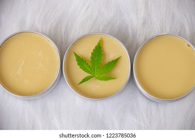 Cannabis hemp creams with marijuana leaf over white background - cannabis topicals concept