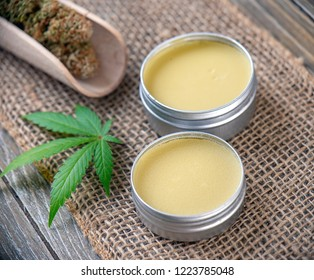 Cannabis hemp creams with marijuana leaf and nugs over burlap background - cannabis topicals concept