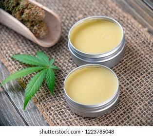 Cannabis hemp creams with marijuana leaf and nugs over burlap background - cannabis topicals concept