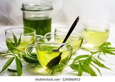 Cannabis herbal tea served in glass teacups with marijuana leaves