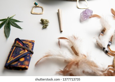 Cannabis Joint and Bud on a white table with feathers, turquoise earrings, marijuana leaf, crystal and a weed pouch for festivals