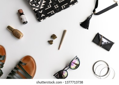 Cannabis Joint and buds on a white background with a tassel choker, sandals, cat eye sunglasses, bangles, and a festival bag and weed pouch.
