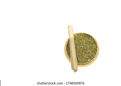 Cannabis joint cigarette on top of marijuana grinder full of well shredded cannabis buds isolated on white background