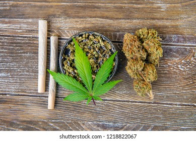 Cannabis joints with fresh nugs and grinder over wood background