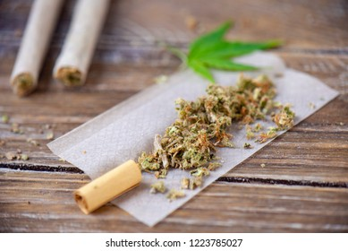 Cannabis joints with rolling paper over wood background - medical marijuana concept