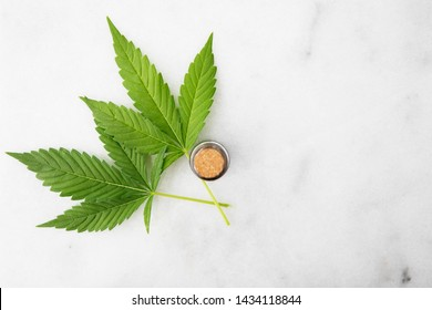 Cannabis leaf with bottle of CBD oil on marble surface with copy space viewed from directly above