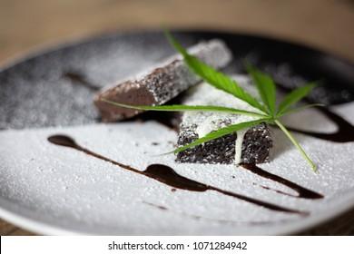 cannabis leaf on a marijuana brownie on wooden table