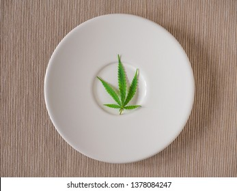 cannabis leaf on white plate. Top view. concept of marijuana use for medicinal purposes. to increase appetite and reduce pain.