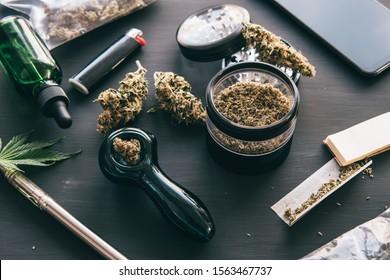 Cannabis legalisation. CBD and THC on buds in cannabis. Macro Cannabis buds weed on black wood background. Marijuana smoking pipe