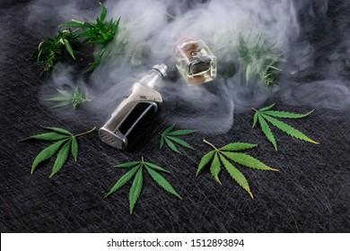 Cannabis liquid. Vape CBD or THC, Vaping Marijuana and Hemp. Against a Dark Background. Thick steam. Horizontal orientation