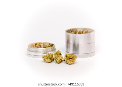 Cannabis or marijuana buds and metal grinder against white backdrop.