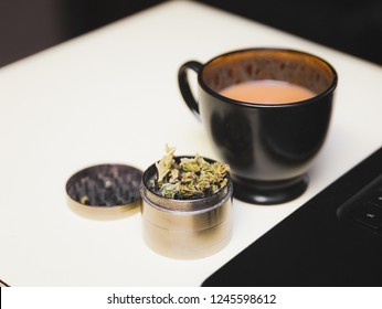 Cannabis or marijuana flower in a steel grinder on a desk, next to a cup of coffee and a laptop.