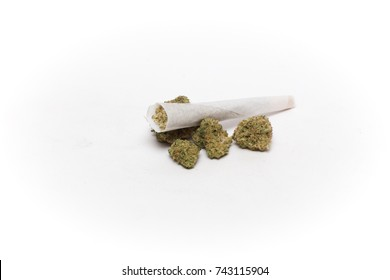 Cannabis or marijuana joint sitting on top of buds (flowers) against a white background.