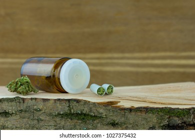Cannabis medicine - cannabis flower in the  apothecary jar and capsules with marijuana on the fresh natural piece of wood, wooden natural background.