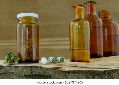 Cannabis medicine - cannabis flower in the jar, pills and antique apothecary bottles with marijuana resin oil on the fresh natural piece of wood, wooden background.