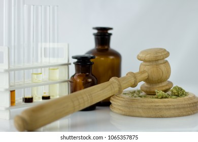 Cannabis oil with  apothecary jar and wooden judge hammer with sound block on the white mirror background -  legal and illegal cannabis.
