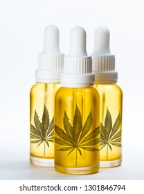Cannabis oil bottled in small dropper jars with a marijuana leaf in the front of the golden oil