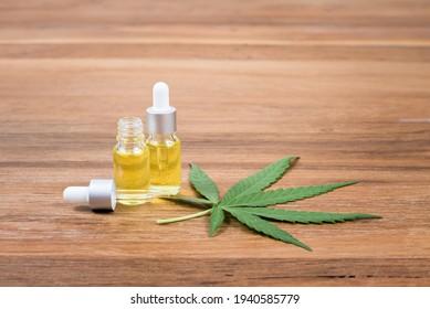 Cannabis-Öl-Extrakte in Tröpfchenflaschen und Cannabisblätter auf Holzhintergrund
