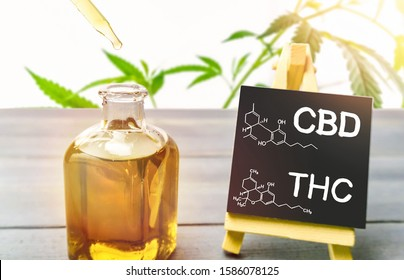 Cannabis oil in glass bottle and chalkboard with molecule drawing of THC and CBD on wooden table