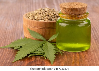 cannabis oil with cannabis seeds and leaves on wooden background