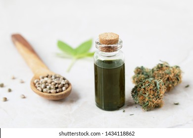 Cannabis oil in small bottle with cannabis bud and seeds