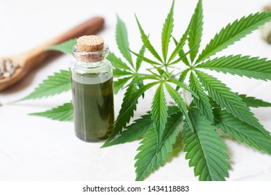 Cannabis oil in small bottle with cannabis leaves.
