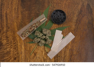 Cannabis sativa weed leaf and flower buds on wooden background with grinder and large smoking papers, copy space