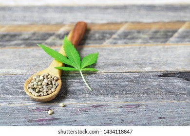 Cannabis seeds in a wooden spoon with leaf on a wooden surface with copy space.