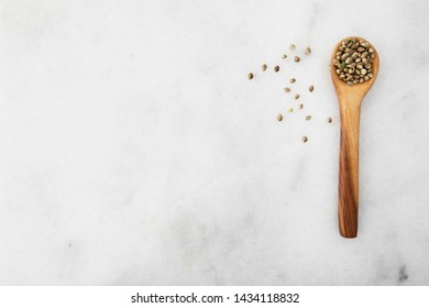 Cannabis seeds in a wooden spooon on a light marble surface with copy space, viewed from directly above.