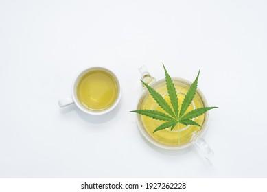 Cannabis-Teekanne mit grünem Marihuana-Blatt auf weißem Hintergrund, Kopienraum