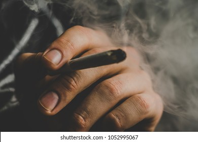 cannabis weed A man smokes, a joint and a lighter in his hands. Smoke on a black background. Concepts of medical marijuana use and legalization of the cannabis. On a black background