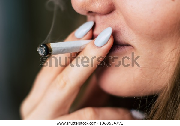 cannabis weed A woman smokes, a joint and a lighter in his hands. Smoke on a black background. Concepts of medical marijuana use and legalization of the cannabis. On a black background