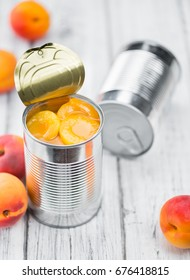 Canned Apricots on rustic wooden background (close-up shot)