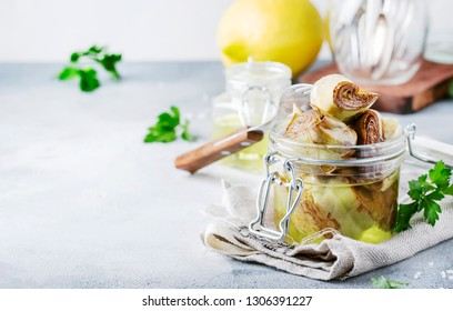 Canned artichokes in olive oil, in glass jar with fork, gray kitchen table background, selective focus