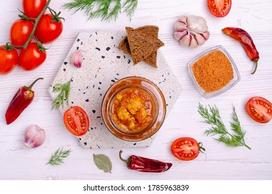 Canned cauliflower with vegetables in tomato sauce in a jar on a light wooden background. Selective focus.