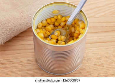 Canned Corn.  Corn in an open can with spoon. Close up.