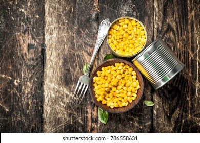Canned corn in a tin can with fork. On a wooden background.