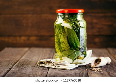 canned cucumbers in a jar on a wooden background, harvesting vegetables, pickles