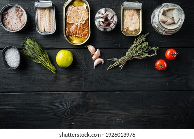Canned fish with different assortment types of seafood set, on black wooden table background with herbs and ingredients, top view flat lay, with copyspace and space for text