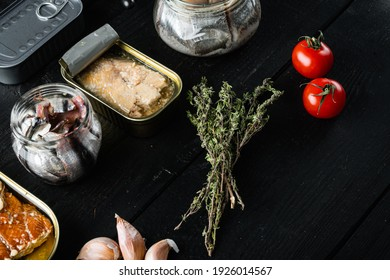 Canned fish, top American preserves set, on black wooden table background with herbs and ingredients