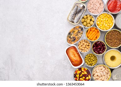 Canned food on stone background, top view with copy space
